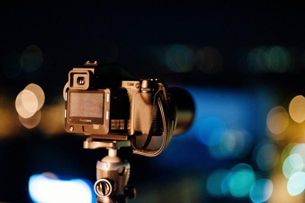 Caméra sur trépied avec des bokeh de lumière en arrière-plan, ambiance nuit